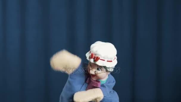 Stará žena maňáska se objeví na scéně, aby odhodil pohyby na modrém pozadí