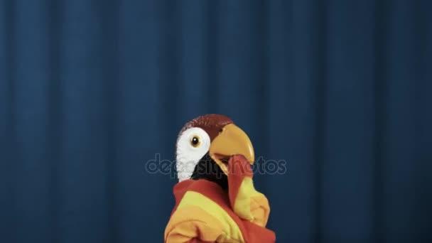 Maňáska papouška běží na scénu vlny a třít ruce na modrém pozadí