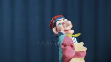 Objeví se na scéně s modrým pozadím, s pozdravem publikum šašek maňáska