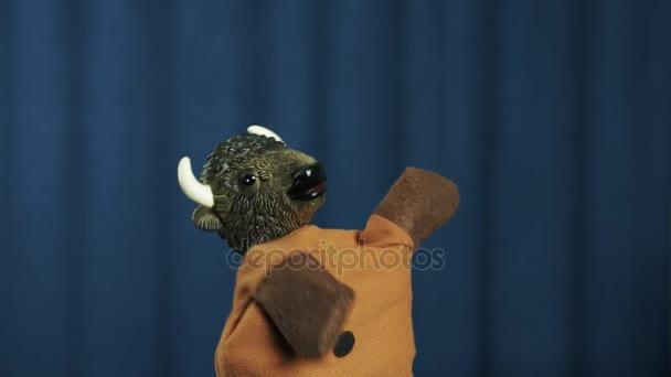 Ox maňáska hraje vzduch kytara a třepe hlavou na scéně s modrým pozadím
