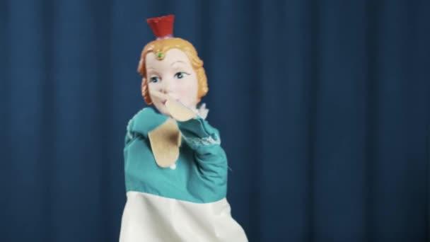 Princezno maňáska pozdrav publikum na modrém pozadí, mávat a pěšky