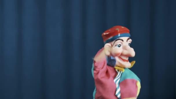 Petruška maňáska mává ruku na rozloučenou a odkráčel scénu s modrým pozadím