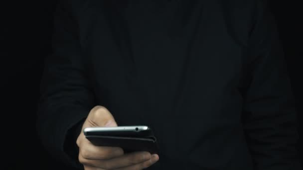 Male hand in long sleeve jacket using cased silver smartphone with thumb