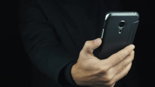 Male hand in long sleeve jacket move cased smartphone, filming or signal search