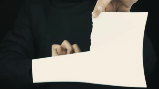 Male hands in long sleeve jacket slowly ripping paper sheet, toss pieces