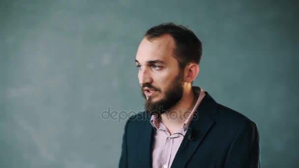 Szakállas férfi kabát és csíkos inget beszél, ki kamera Mutatóujj pont