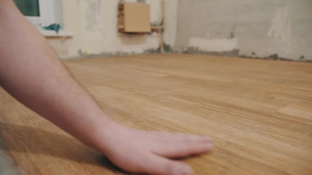 Mužských rukou hladím dřevěné podlahy kontrolu prachu