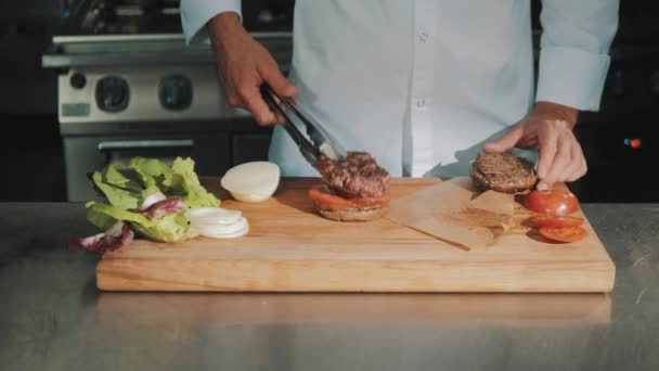 Male cooking chief in white robe making hamburger, puts grilled meat