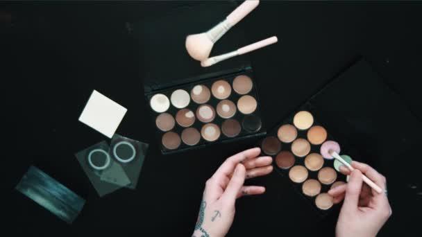Vytetované ženské ruce tryes make-upu štětec eyeshadow prášek černý stůl