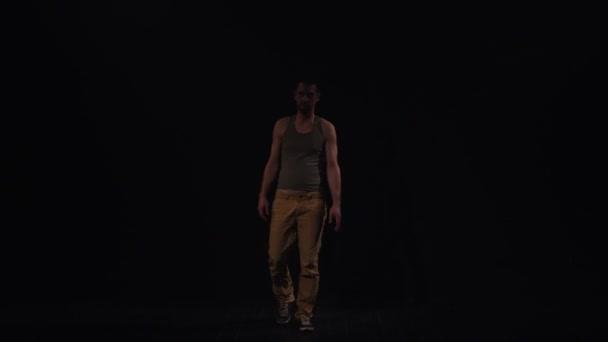 Man in short grey tank top and yellow pants talking shrugs in black room