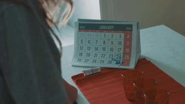 Woman looking at calender of january 2015, 24 date circled with mark sport day
