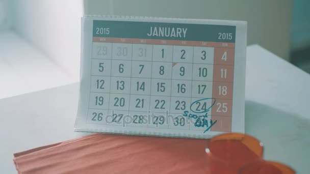 Calendar page of january 2015 on kitchen table . Date 24 circled as sport day