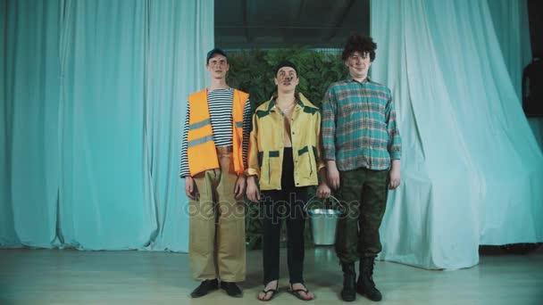 Tři vtipné muže oblečená jako špinavé silnice pracovníci skok současně na scéně