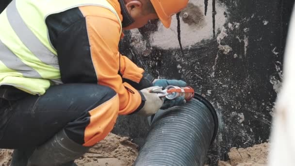 Worker applying sealant on stitch between ribbed plastic pipe and concrete  hole