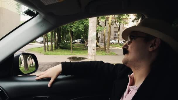 Man with mustache in dinner jacket, hat, glasses sitting in car and sing. Parody