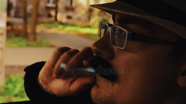 Man with mustache in hat, glasses sitting in car with cigarette. Summer. Parody