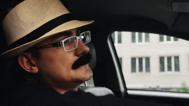 Adult man with mustache in hat, glasses sitting in car. Summer day. Parody