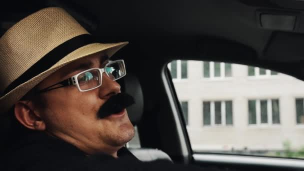 Man with mustache in hat, glasses sitting in car at window and sing. Parody