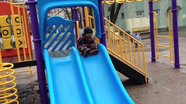 Little boy slide from hill on children playground and fall in dirty puddle.