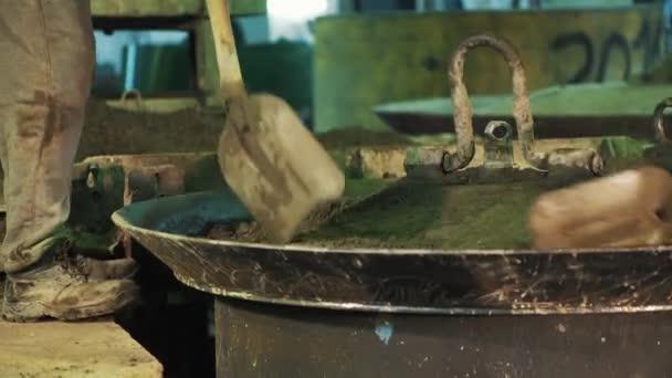 Arbeiter mit Schaufel Dig schütteln Zementpartikel auf Metall-Kessel ...