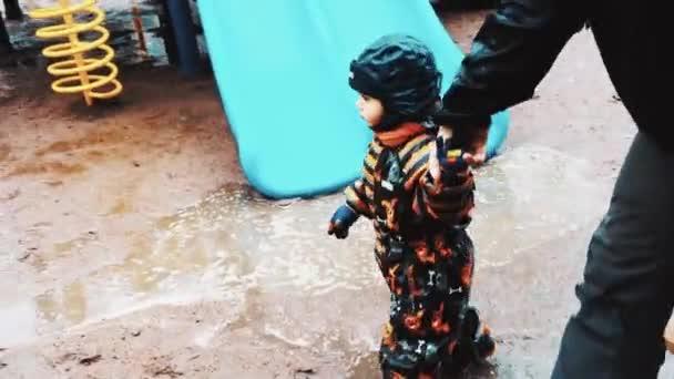 Otec držel ruku malého chlapce na dětské hřiště. Rodina. Prší – počasí