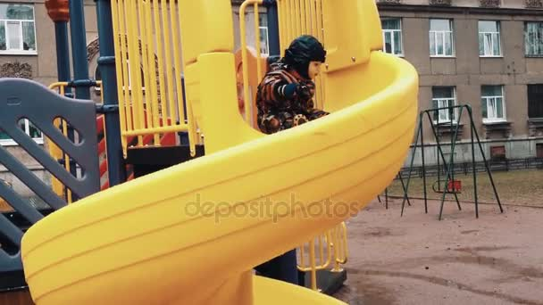 Little boy slide from kids hill on children playground and fall in dirty puddle.