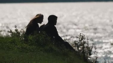 Couple sits on grass in front of water of a lake on a summer windy day