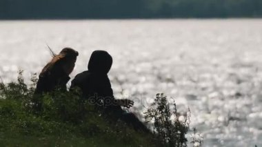 Couple silently sits on grass in front of water of a lake on a summer windy day