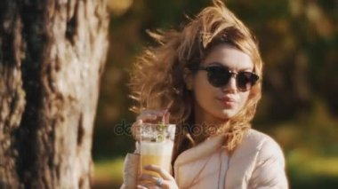 Girl in sunglasses drinking milkshake with a straw outside on a windy summer day