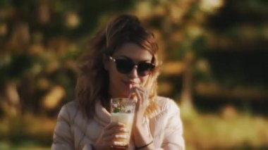 Woman in sunglasses drinking cocktail with a straw outside on a windy summer day
