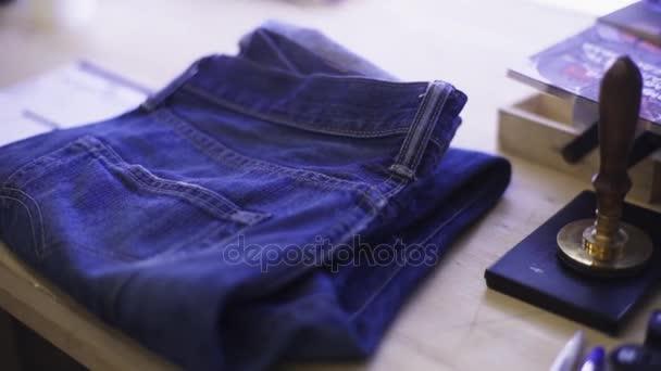 Piegato jeans blu magra sulla scrivania tavolo in legno