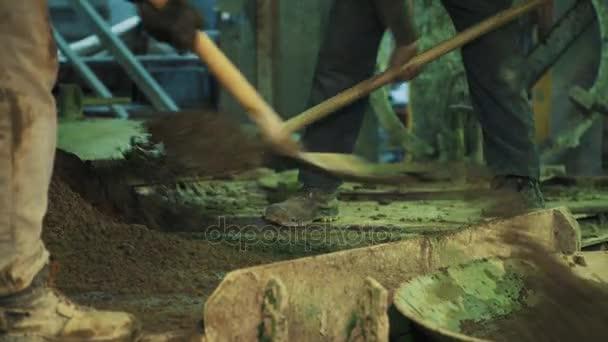 Zwei Arbeiter schnell werfen Zement auf Metall Kessel Deckel ...