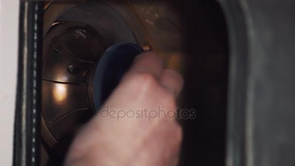 Mužské ruky dát čočky do kovových trysek v pračce v továrně