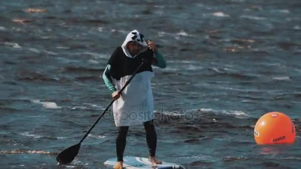 Man wears panda suit on a surfboard rides around beacon rowing with a paddle