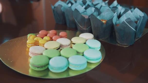 Vícebarevné makronky a mini zákusky na kuchyňském stole