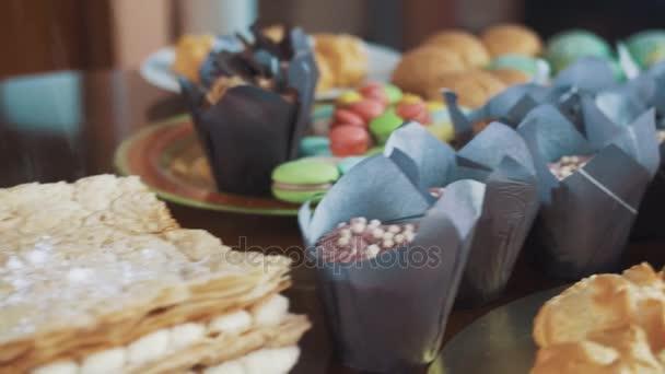 Cukr práškový sypat na vrstvený dort na stůl se spoustou cukrářských výrobků