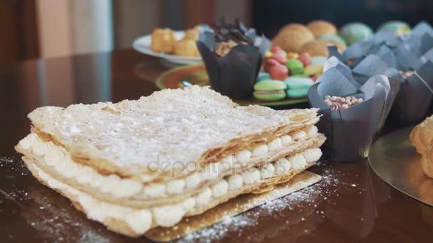 Cukr práškový sypat na vrstvený dort na stůl se spoustou dezert produktů