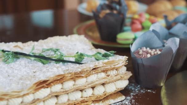 Ženské ruce zdobí vrstvený dort v cukru prášek s borůvkami