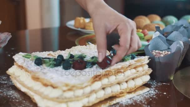 Ženské ruce zdobí vrstvený dort v prášku cukru s červené želé