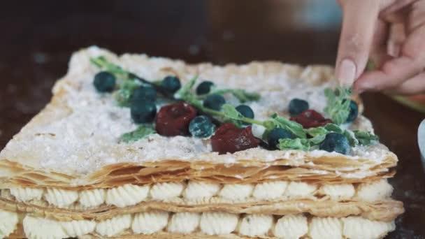 Ženské ruce zdobí vrstvený dort v prášku cukru s lístky máty