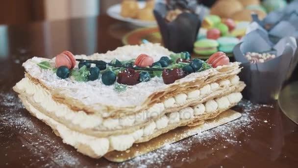 Vrstvený dort zdobený bobule, máta a cukroví na stůl s pekárna