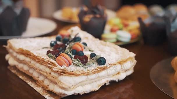 Vrstvený dort zdobený bobule, máta a cukroví na tabulce s cukrovinkami