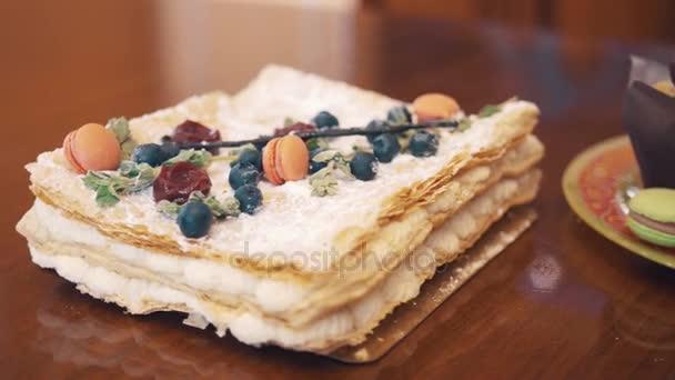 Cukru prášek dort s ovocem, máta a cukroví na stůl s pekařské výrobky