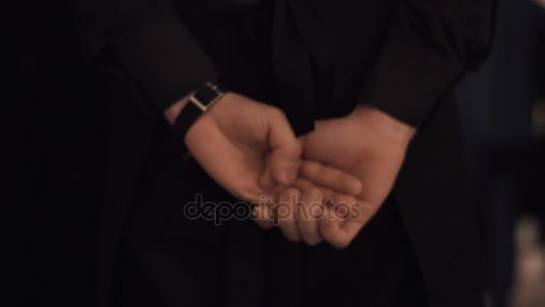 Číšník nebo kněze v černých šatech, drželi se za ruce za zády, se třese