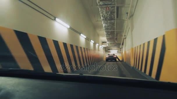 Dashcam view, car driving through underground parking corridor