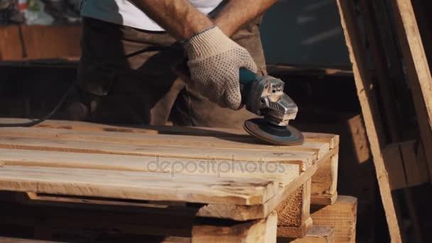 Tesař člověk použít úhel mlýnek stroj na hladké dřevěné prkna struktury