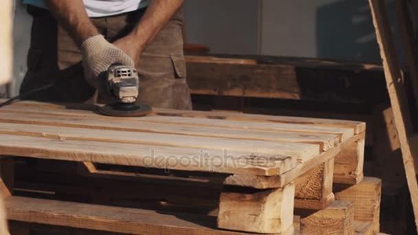 Architekt muž použít úhel mlýnek stroj k vyhlazení struktury Dřevěná prkna