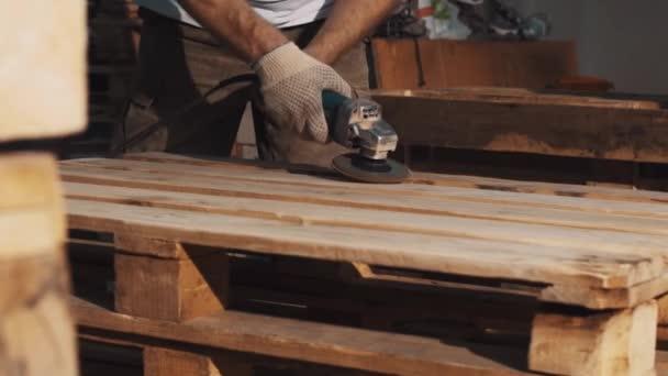Tischler Mann verwenden Winkelschleifer Maschine, um Holzstäbe Struktur glätten