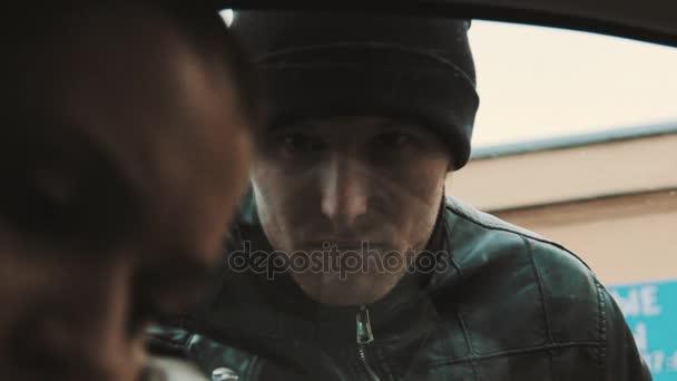 Tajemný kriminální muž dívá na ženu, která na mobil v autě
