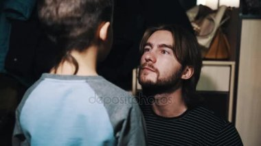 Child son talks to long haired father in apartment hallway
